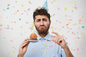 Studio shot of attractive bearded adult birthday guy having birthday party in light room, holding small cupcake in his hand and gesturing with other one, having unhappy sad expression on his face
