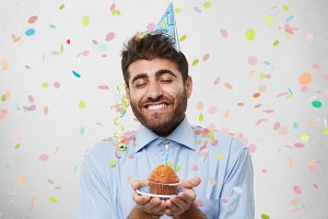 Look at this tasty cake! Pleased man with thick beard and broad smile, holding plate with little delicious cake and candle, closing his eyes with pleasure being happy to celebrate his son`s birthday