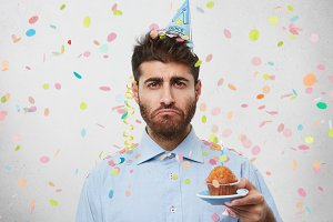 Upset young man wearing party cap and shirt, holding little cake with candle, having his birthday, curving his lips with with sullen expression, being lonely. Gloomy man with tasty cake being alone