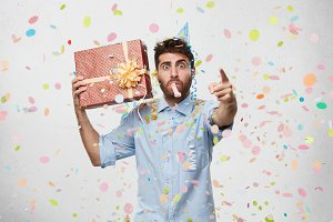 People, partying, fun and entertainment concept. Picture of handsome unshaven young man in blue shirt pointing finger at camera, holding present in wrapped box, congratulate you on your birthday