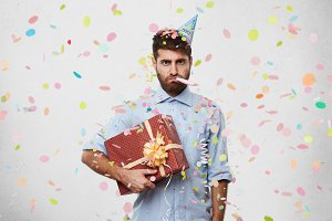 Unhappy displeased young male with beard wearing cone hat on head and holding party horn in mouth, looking at camera with bored dissatisfied expression, carrying box of birthday present under his arm