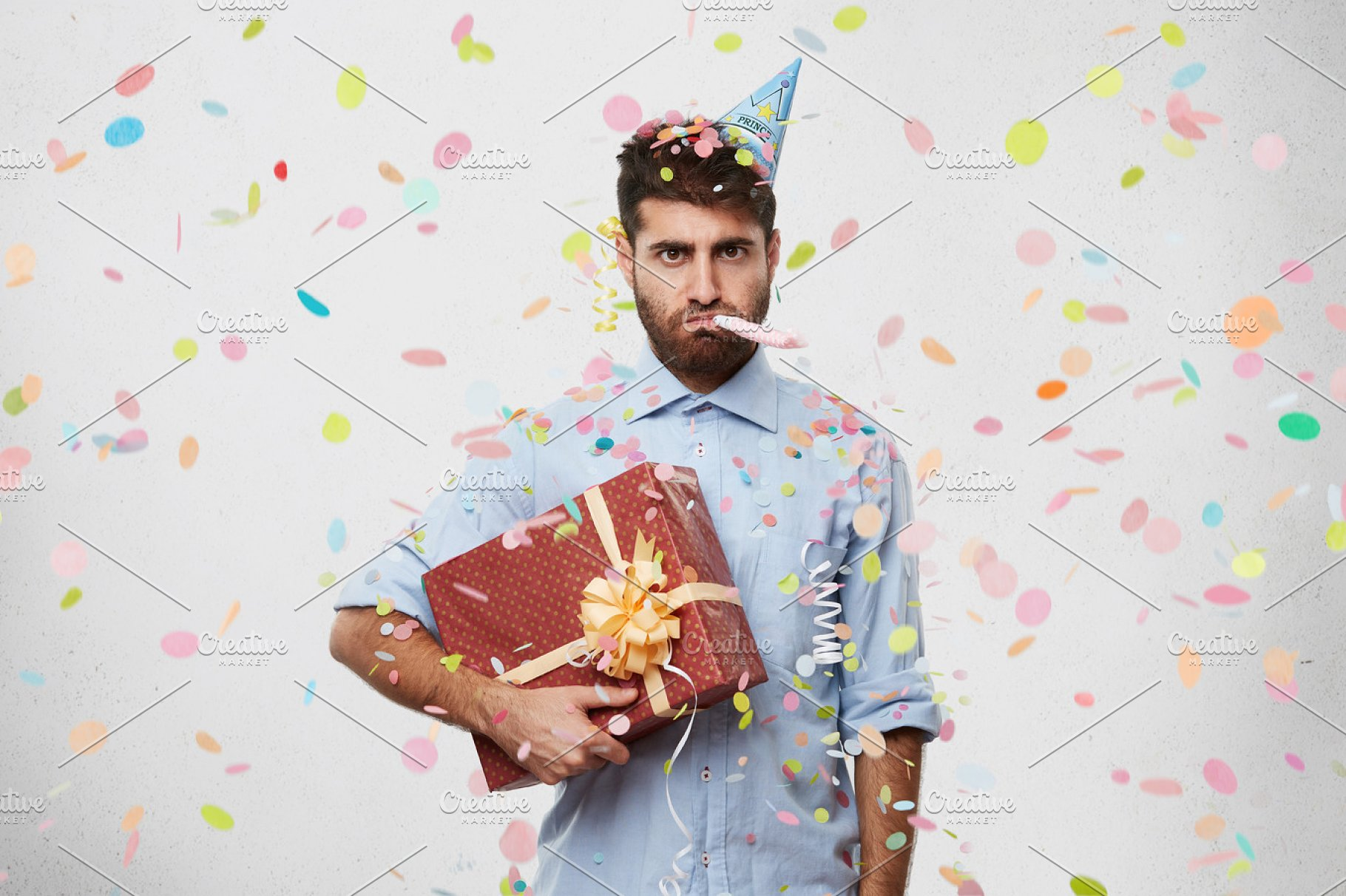 Unhappy displeased young male with beard wearing cone hat on head ... db9e7f6c7c99