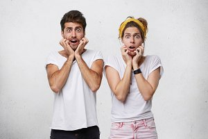 Portrait of emotional surprised young man and woman keeping eyes popped out and holding hands on their faces, feeling terrified after they received some unexpected shocking news. Body language