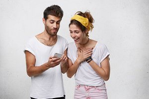 So cute! Portrait of warm-hearted kind young woman wearing yellow headband holding hand on her chest and exclaiming while watching pictures on mobile phone held by her attractive bearded male friend