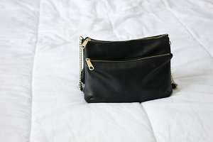 Black Purse On White Bed