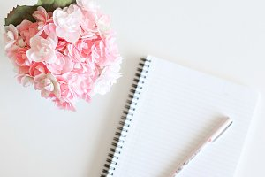 Flowers & Blank Notebook On Desk