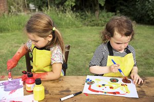 Cheerful kids painting in a garden