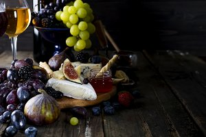 Grape, cheese, figs and honey with a glasses of white wine