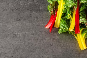 Rainbow chard, colorful eating and healthy diets. Dark background. A delicious diet.