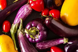 Small eggplant, yellow zucchini, tomatoes and purple pepper. Dark background. Vegetarian food from the village.