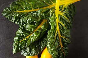 Yellow zucchini, chard. Dark background. Vegetarian food from the village.