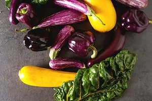 Small eggplant, yellow zucchini, chard and purple pepper. Dark background. Vegetarian food from the village.