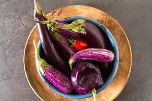 Small eggplants, tomatoes. Dark background. Vegetarian food from the village.