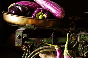 Small eggplant on the scales. Dark background. Vegetarian food from the village. Delicious dinner for the whole family.