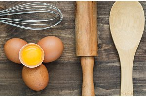 Top view on fresh eggs and rustic wooden kitchen utensil.