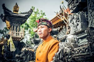 Close up portrait of balinese indonesian man posing at the tradtional temple. Tropical Bali island, Indonesia.