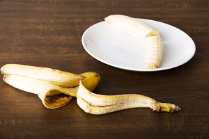 Pilled banana on a plate and its skin lying next to it.