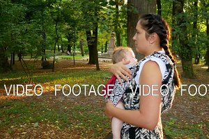 Mother walks in the park with her baby