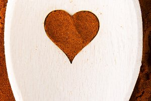 Heart shape made from spice on a wooden spoon.