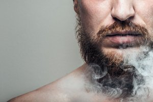 Close-up, portrait of unrecognizable man with a beard, face in cigarette smoke. Quitting smoking, harmful habit