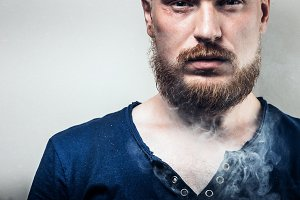 Close-up, Portrait of a serious man with a beard, face in cigarette smoke. Quitting smoking, harmful habit