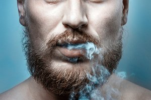 Close-up portrait of  handsome man with  beard whose cigarette smoke comes out of his mouth. Harmful habit