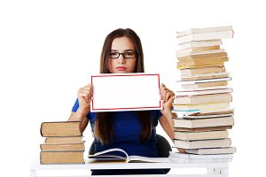 Beautiful young woman stuydent wih stack of books and holding co