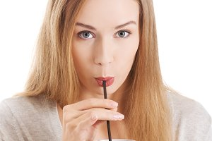 Beautiful woman is drinking from a cup with  straw.