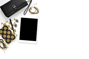 Flat lay photo of stylish office white desk with wallet, Women's jewelry, tablet and gold notebook copy space background