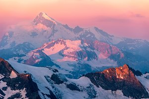 Pink sunrise in mountains.