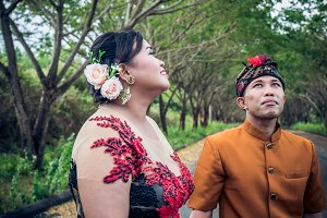 Lovely honeymoon balinese couple in traditional clothes together in nature. Bali island, Indonesia. Asia.