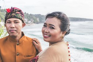 Close up portrait of Lovely honeymoon balinese couple in traditional clothes together in nature. Bali island, Indonesia. Asia.