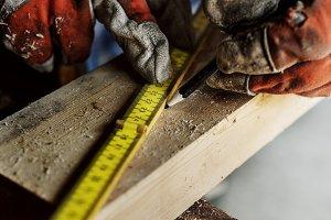 Carpenter checks wood size for work