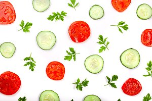 Cucumber and tomato slices with parsley leaves isolated on white background. Top view