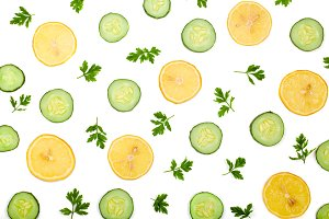 Cucumber and lemon slices with parsley leaves isolated on white background. Top view