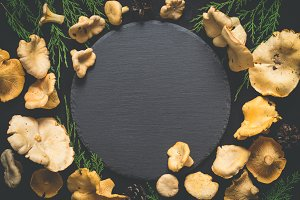 Food background with wild mushrooms chanterelles around a slate cutting board