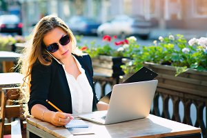 Business woman on the street in the computer at a table in a cafe