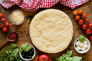 Pizza dough and ingredients for making pizza on wooden table