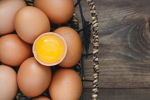Top view of fresh eggs in an iron vintage basket on wooden boards. Rustic style.