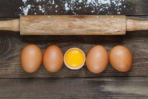 Top view on fresh eggs in a row and rolling pin on a wooden table. Cooking concept.