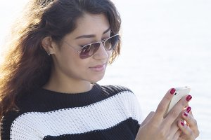 Girl talking on mobile phone at sea