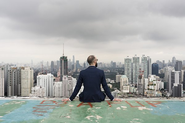 Businessman Sitting on Rooftop