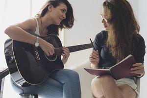 Lesbian couple playing guitar