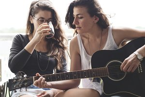 Lesbian couple playing guitar
