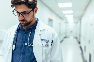 Male doctor in hospital corridor.
