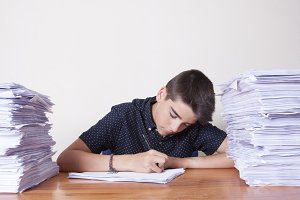 child student on the desk with stacked papers