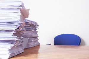 desk with stacked papers, work and stress