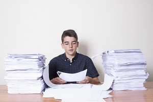 student on the desk with stacked papers
