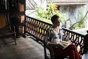Woman reading a book on the balcony