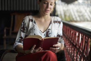 woman reading book on the balcony